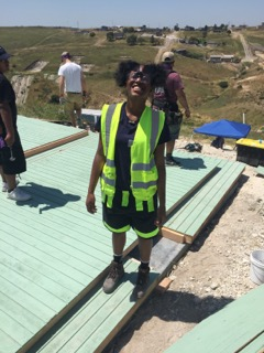 A Colorado Uplift student smiles broadly while standing on a foundation of service and leadership while building homes in Tijuana
