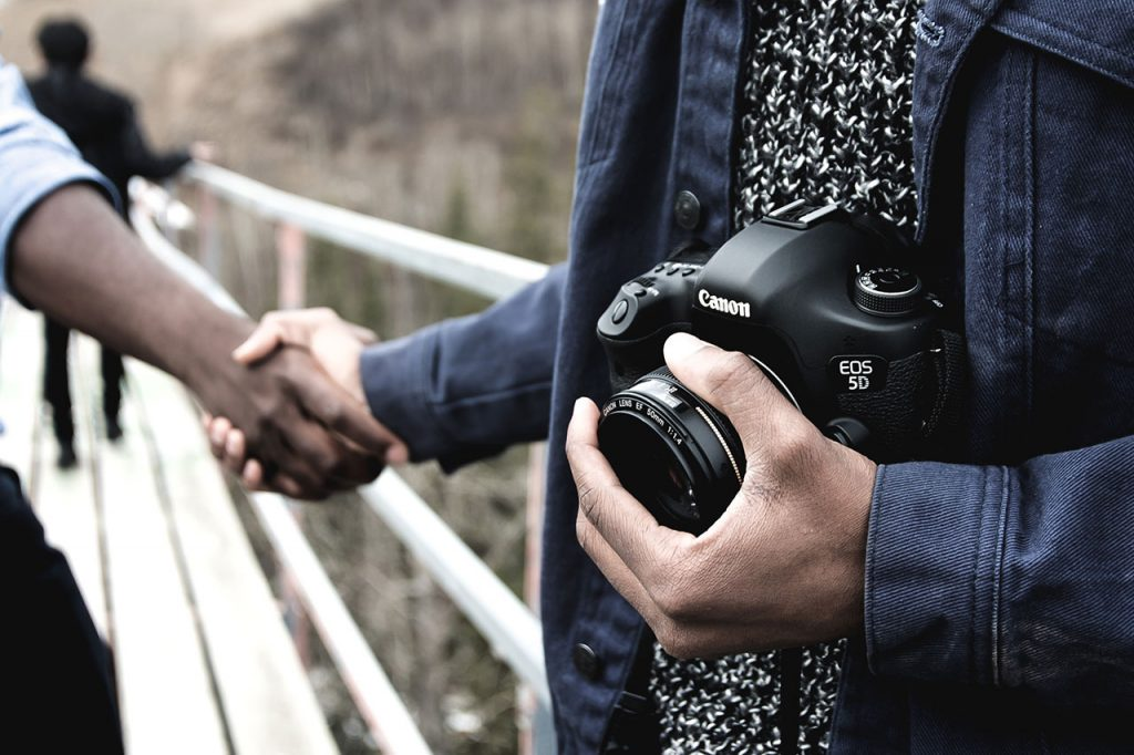 Friendly photographer shakes hands. With what lens will observers view your second-hand relationships?