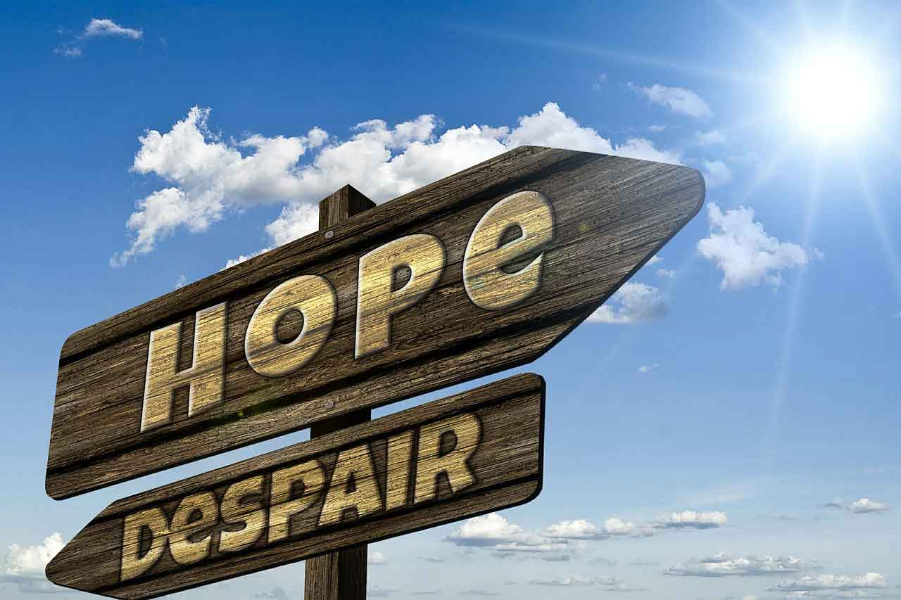 Choose optimism when you face a wooden sign post pointing the ways to hope and despair