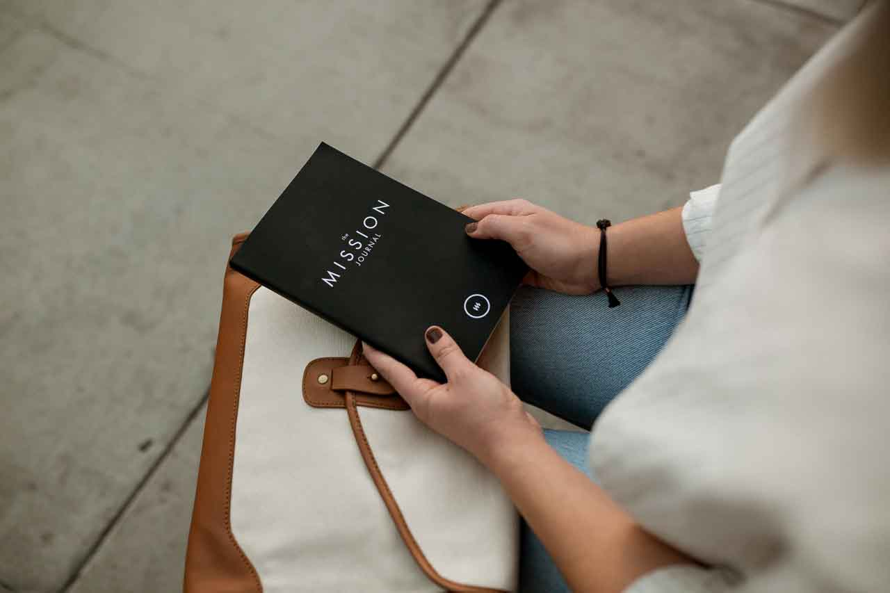 Woman holds a black book etched, representing purpose in work