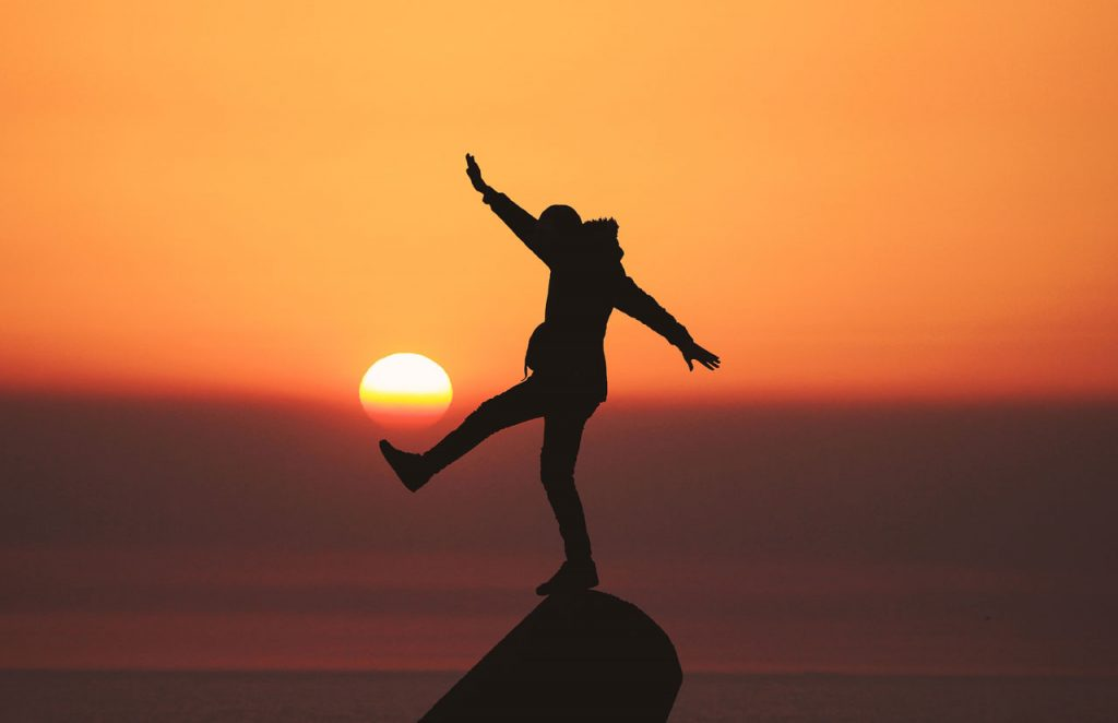Man performing a balancing act on narrow rock against sunset